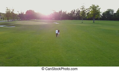 Aerial View Of Young Couple Walking In Summer Park, Circling...