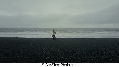 Aerial view of young couple walking on black volcanic beach. Man and woman have a date on shore of the sea in Iceland.