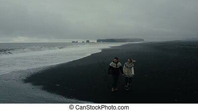 Aerial view of young couple walking on the shore of the sea in Iceland. Man and woman look to the wave at black beach.