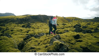 Aerial view of young couple walking on the volcanic lava field in Iceland. Man and woman enjoying the landscape.