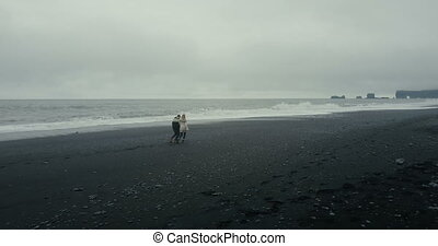 Aerial view of young couple walking, running on black volcanic beach in Iceland. Tourists in lopapeysa enjoy the waves.