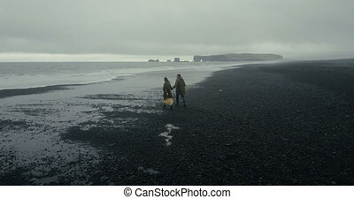 Aerial view of young stylish couple walking on the black volcanic beach in Iceland. Man and woman running from the wave.