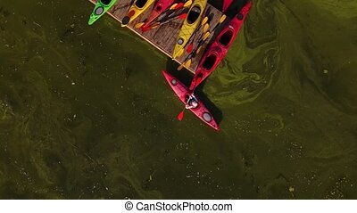 Aerial view of young woman is kayaking on lake in summer.