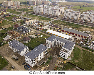 Aerial view on a construction site in progress. Industrial Zone. Against the background of built houses