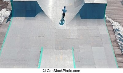Aerial view on a skatepark. BMX rider going downhill from...