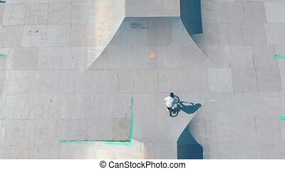 Aerial view on a skatepark. BMX rider in white hoodie...