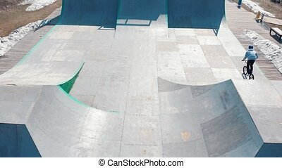 Aerial view on a skatepark. Young BMX rider riding on the...