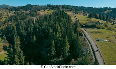 aerial view on byroad mountain village - drone flies over a...