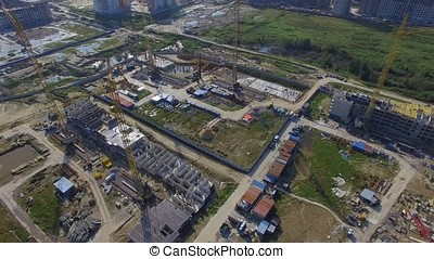 Aerial view on construction building. Construction site workers, aerial, Top View. Overhead view of construction site with large crane. Aerial view of collapsed floor on a building site and builders working.