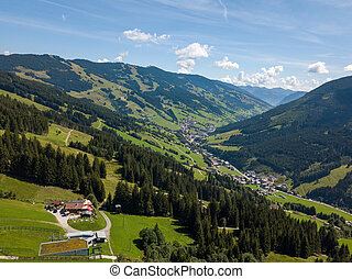 Aerial view on cozy hut with mountain panorama from Hinterglemm to Saalbach in the Alps in Austria. on a sunny summer day