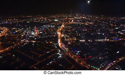 Aerial view on Dubai from flying airplane at night