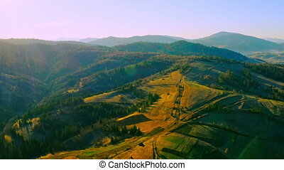 panoramic view on mountains with coniferous trees beautiful nature landscape at sunrise in spring season lens flare