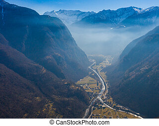 aerial view on Maggia valley in Ticino with snowcapped mountains and blue sky