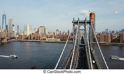 Aerial view on Manhattan bridge in New York, America. Drone flying over the East river, boat riding through.