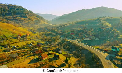 drone flies above small town in mountains area highlands in soft sunlight spring season outdoors