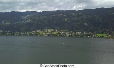 Aerial view on Ossiacher Lake in Carinthia, Austria with a sailing boat on a summer day with great cloudscape.