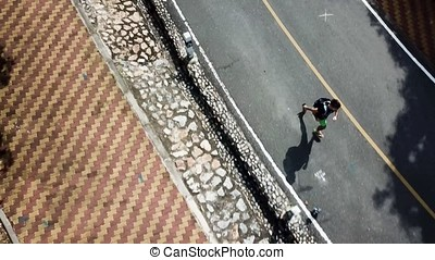 Aerial view on running man at the street, sunny day. A...