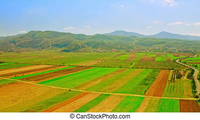 drone flies above agricultural fields green and yellow with young plant on the background village and mountains landscape in spring season