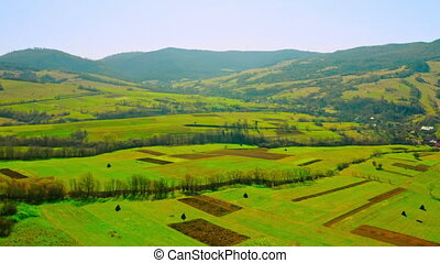 drone flies above agricultural field in spring season mountains landscape forest daytime