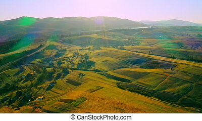 drone flies above fields houses forest in countryside mountains landscape at sunrise sun rays shine on village lens flare
