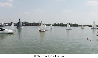 Aerial view on sailing regatta near island. Sailing ship yacht with white sails involved in water sports. Marine navigation in sunny summer day.