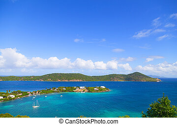 Aerial view on shallow waters of Caribbean Sea surrounding St Thomas Island, US VI. Motorboats at the sea near the tropical island.