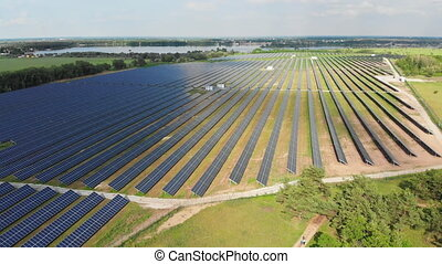 Aerial view on Solar Power Station in Green Field near River...