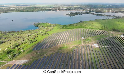 Aerial view on Solar Power Station in Green Field near River at Sunny Day. Fly over Solar Farm. Solar Panels Stand in Row for Power Production. Renewable green energy. Alternative energy sources