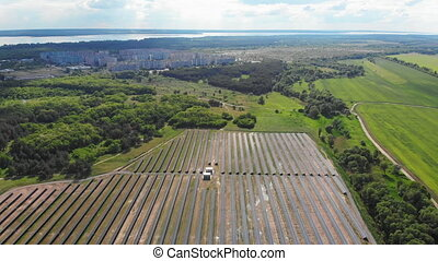 Aerial view on Solar Power Station in Green Field near Small...