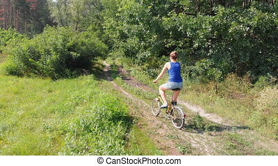 Aerial view on the Girl is Riding a Retro Bike on a Dirt Road in a Field near the Forest.