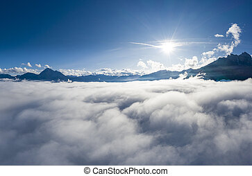 aerial view over cloud bank to tirol mountain alps with sun beams