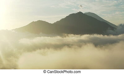 Aerial view over clouds volcanoes at sunrise Indonesia -...