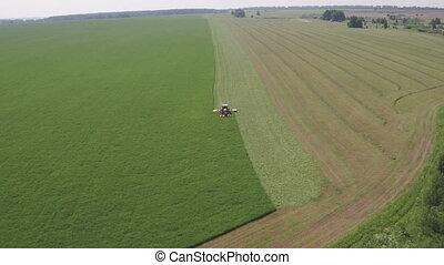 Aerial view over Combine harvester unloading corn in tractor...