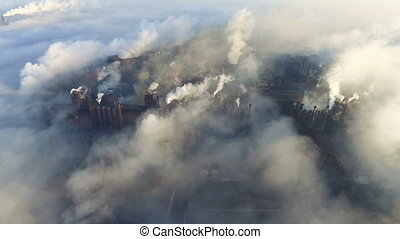 Aerial view over dirty smoke and smog from pipes of steel...
