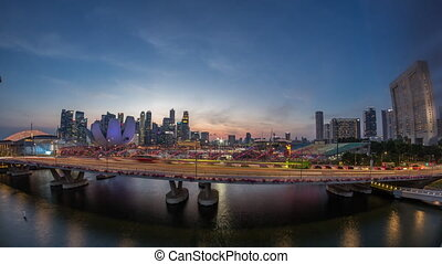 Aerial view over Helix Bridge and Bayfront Avenue with traffic day to night timelapse at Marina Bay, Singapore