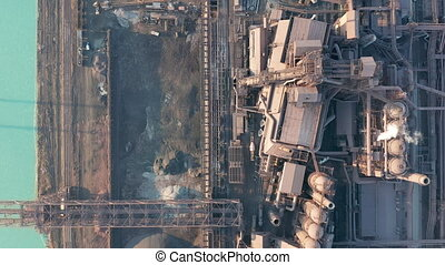 Aerial view over industrialized city with air atmosphere and river water pollution from metallurgical plant near sea. Dirty smoke and smog from pipes of steel factory and blast furnaces. Ecological