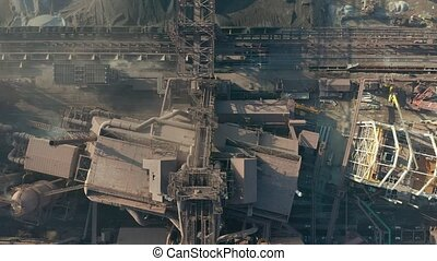 Aerial view over industrialized city with air atmosphere and river water pollution from metallurgical plant near sea. Dirty smoke and smog from pipes of steel factory and blast furnaces.