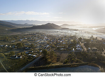 Aerial view over small town in hilly countryside