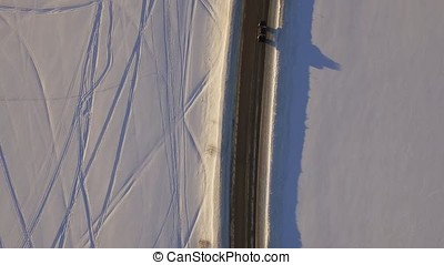 Aerial view over snowy field and road. The car on the road...