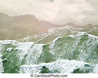 Aerial view over waves breaking onto the beach