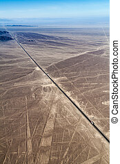 Aerial view Panamericana highway crossing the geoglyphs near Nazca - famous Nazca Lines, Peru. On the right side, observation tower is present.