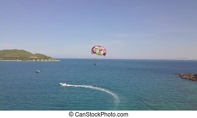 Aerial view parasail flying over blue sea pulled boat. Parasailing in sea bay and green island landscape drone view. Summer activity and extreme entertainment while resting on resort beach.