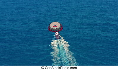 Aerial view. People flying on a colorful parachute towed by a motor boat. Parasailing in blue sky.
