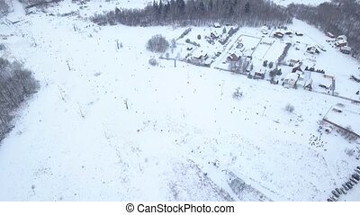 Aerial view people skiing and snowboarding on ski slope on winter ski resort