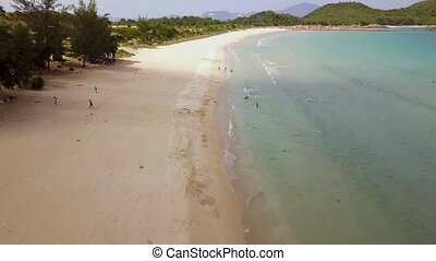 Aerial view people swimming on paradise beach. Drone view blue sea and sandy beach. View from above drone flying over ocean shore.