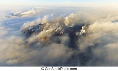 Aerial view. Pipes Throwing Smoke in the Sky. Large Plant on the City.
