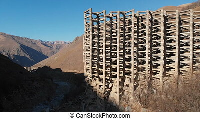 Aerial view protection against mudflow barrier in a gorge in the mountains. Reinforced concrete structure to prevent destruction by natural disaster. Powerful water and mud protection. North Caucasus Russia