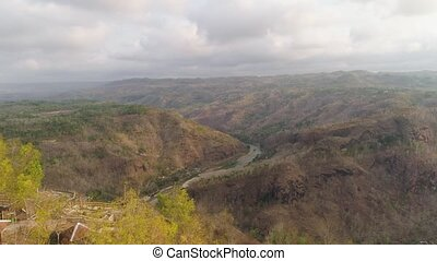 aerial view river Oyo canyon among farm lands rice terraces. river in mountain canyon Kebun Buah Mangunan, gorge, among hills covered with vegetation, trees at sunset. tropical landscape