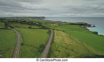 Aerial view road green meadows rise up drone shoot. Car drives along farmland way in Irish coutryside. Dramatic summer scenery of Northern Ireland in pastel tones. Footage shot in 4k, UHD
