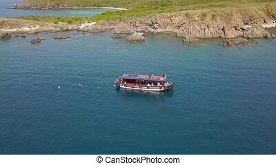 Aerial view sailing ship in blue sea and mountain cliff on shore. Tourist people swimming in clear sea water and boat sail drone view. Beautiful sea bay.